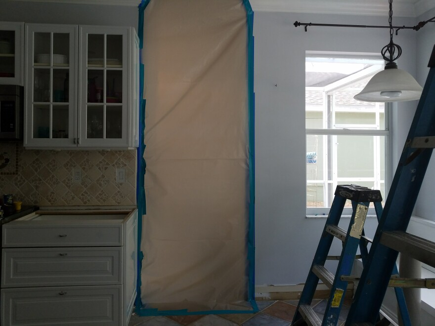 The dining room in this Estero home is cordoned off with tarp, as a water damage repair company removes moldy bamboo flooring.