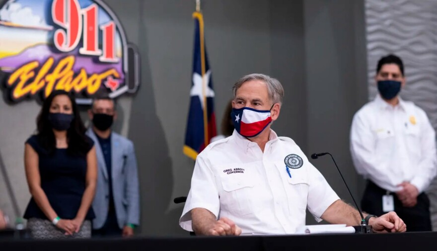 Gov. Greg Abbott wears a Texas flag face mask at a press conference.