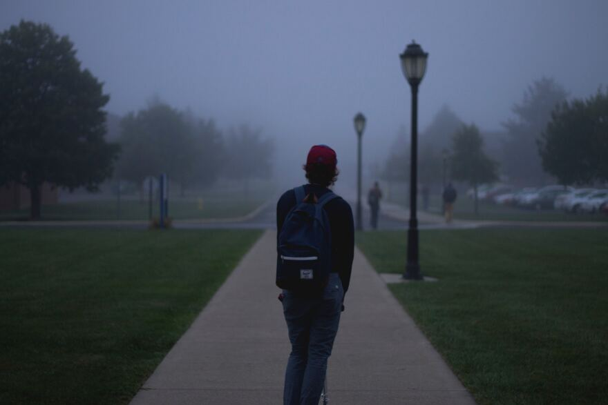 Image of student walking on campus in foggy day.