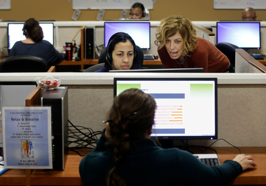 Meg Ivatti (right), a manager at HealthSource RI, the state's insurance exchange, works with Dianiri Paulino to help a caller sign up for coverage in 2014.
