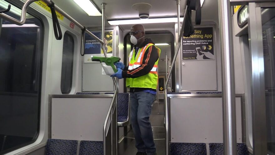 DART employee spays sanitize on targeted areas on train.