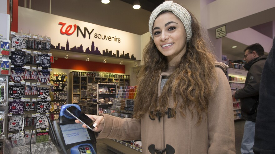 A customer makes a purchase using Apple Pay on her iPhone 6 at a Walgreens store in Times Square last Monday. The mobile payment service has now been blocked by CVS and Rite Aid.