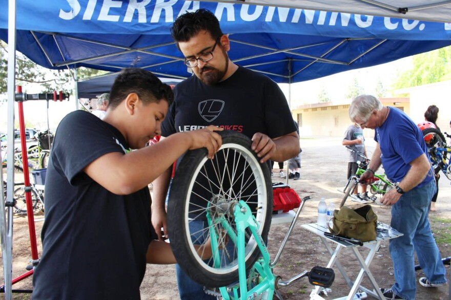 Jaime Rangel helps Gustavo Ruiz, 12, align a tire on his bike, at a recent community event in southeast Fresno, Calif. As manager for Bici Projects, Rangel promotes cycling in the Latino community as a great way to get in shape.