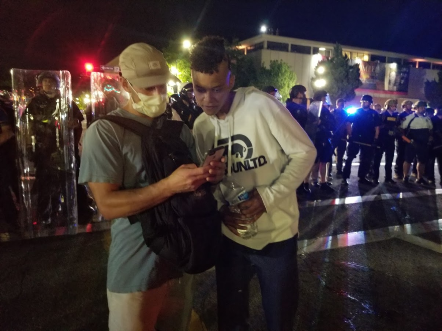 Photo of two people speaking in front of a line of law enforcement officers in riot gear.