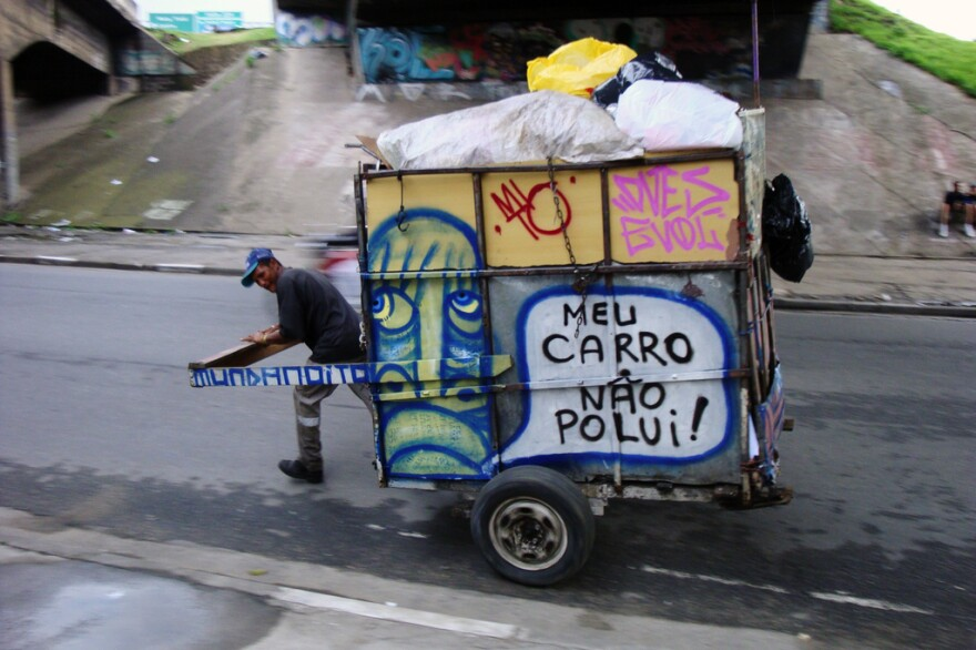 """A waste picker<em></em> wheels a trash cart with Mundano's art and spreads the word: """"My cart doesn't pollute."""""""