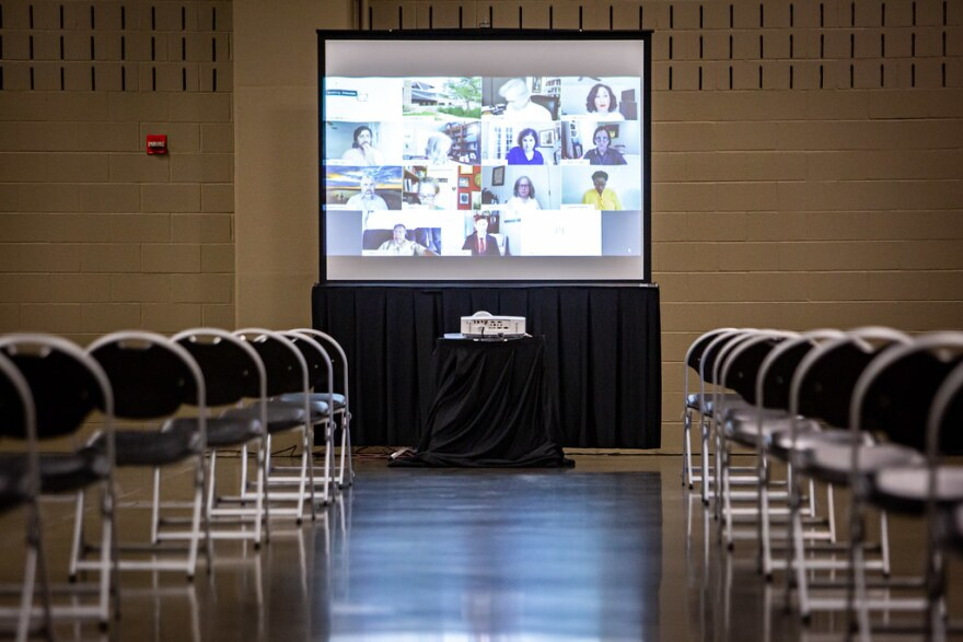 Council members can be seen on a screen in the front of a room at the Palmer Events Center during a virtual City Council meeting.