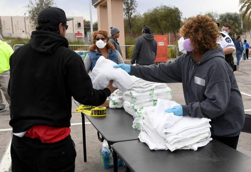 Multi-Agency Coordination Center (MACC) volunteer Bircie Wilson (R) hands out blankets as people arrive at a temporary homeless shelter set up in a parking lot at Cashman Center in Las Vegas, Nevada.