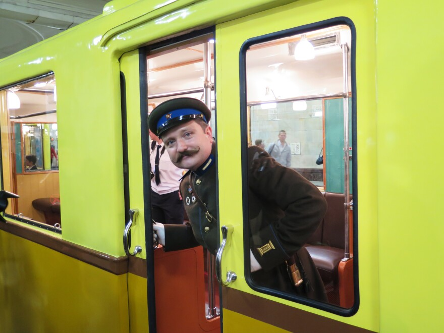 A re-enactor in Soviet costume from the 1930s peers out of a vintage subway car as part of the anniversary celebrations.