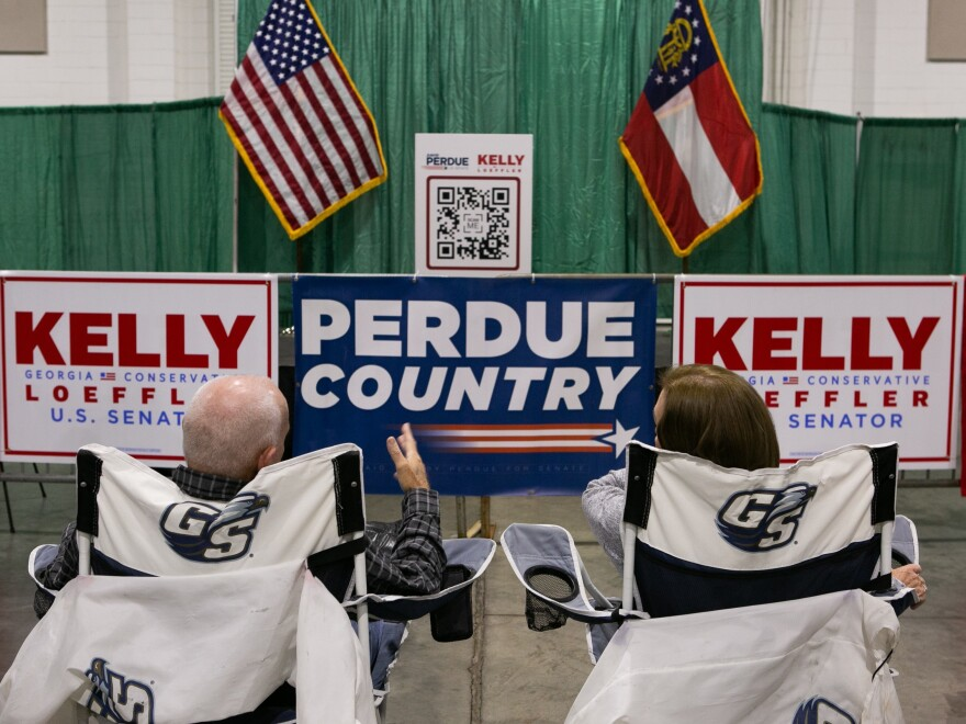 "Supporters Ronnie and Linda Roberts wait for the start of the ""Defend the Majority"" rally for U.S. Sen. Kelly Loeffler (R-GA) and Sen. David Purdue (R-GA) with Sen. Tom Cotton (R-AR) at the Georgia National Fairgrounds and Agriculture Center on Nov. 19."