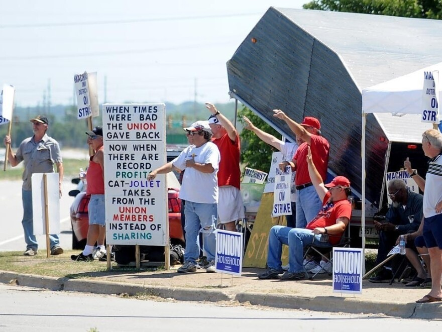 Striking workers picket outside a Caterpillar plant in Joliet, Ill. The work stoppage is now entering its third month.