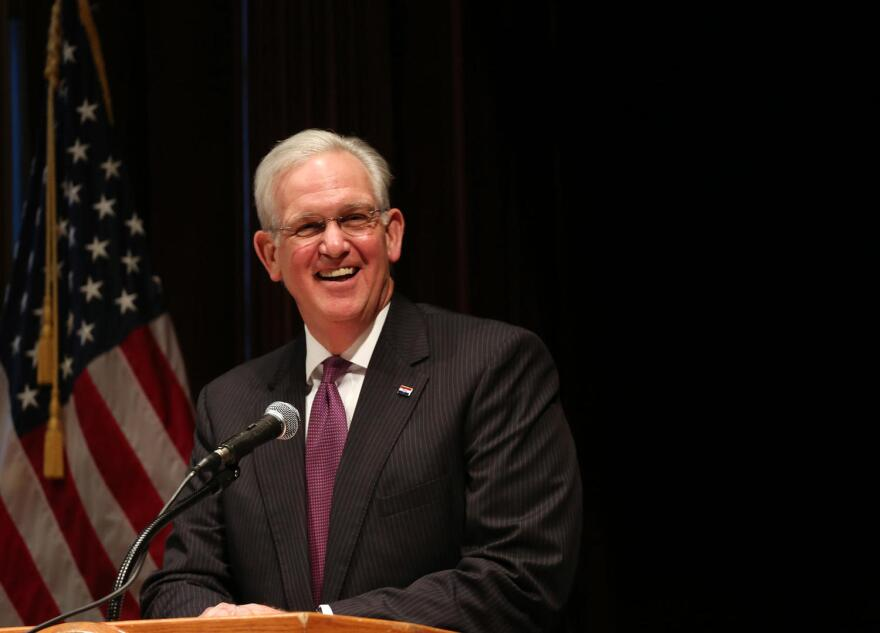 Jay Nixon speaks behind a podium, an American flag is seen in the background.
