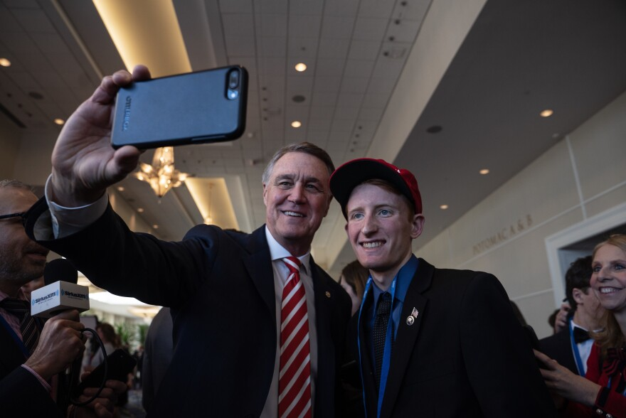 Republican Sen. David Perdue, who spoke about reducing the national debt, takes a selfie with a young MAGA supporter.