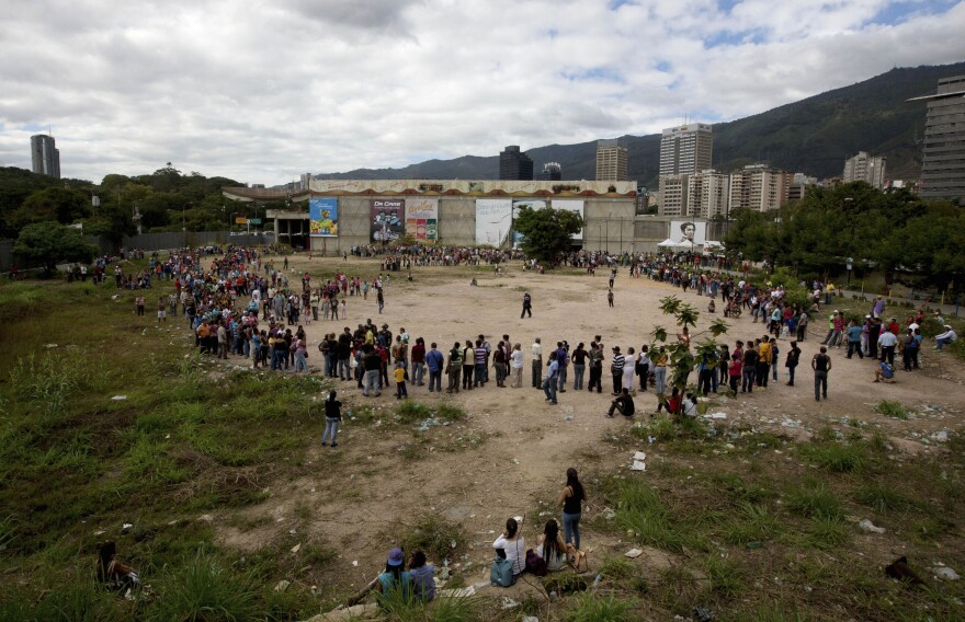 People line up outside the Bicentenario, a state-run supermarket, in Caracas, Venezuela, on Jan. 9. Most of the shortages in Venezuela are driven in part by the country's tight currency controls, which make it hard to get dollars at a subsidized rate for imports while creating a thriving black market for currency.