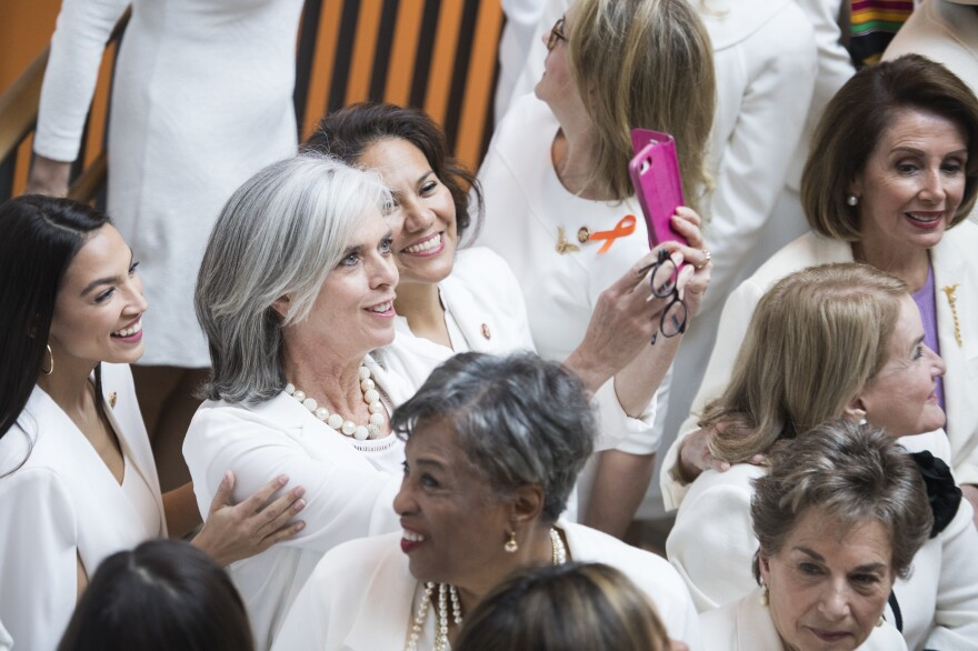 "Reps. Alexandria Ocasio-Cortez, D-N.Y., Katherine Clark, D-Mass., and Veronica Escobar, D-Texas, take a selfie during a group photo of House Democrats in the Capitol Visitor Center wearing ""suffragette white"" to the 2019 State of the Union address."