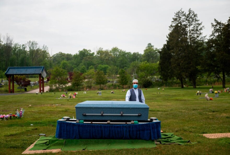 Imam Said Sherzadi  stands alone near the casket of Ghulam Merzazada, at the National Memorial park cemetery in Fairfax, Virginia.