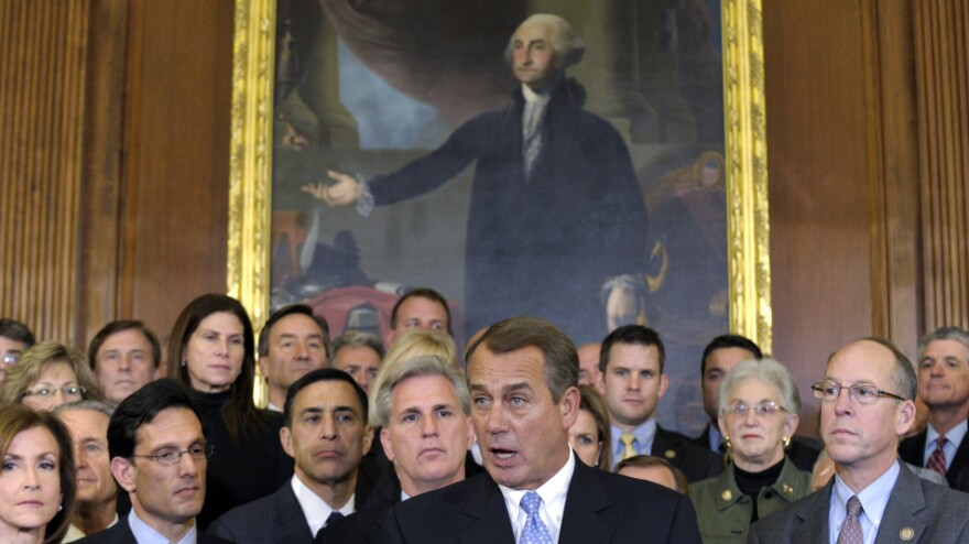 House Speaker John Boehner, surrounded by Republican House members, speaks during a news conference in Washington in December. The House initially rejected a plan to extend a tax cut for two months to buy time for talks on a full-year renewal. It later compromised — a rare event in 2011.