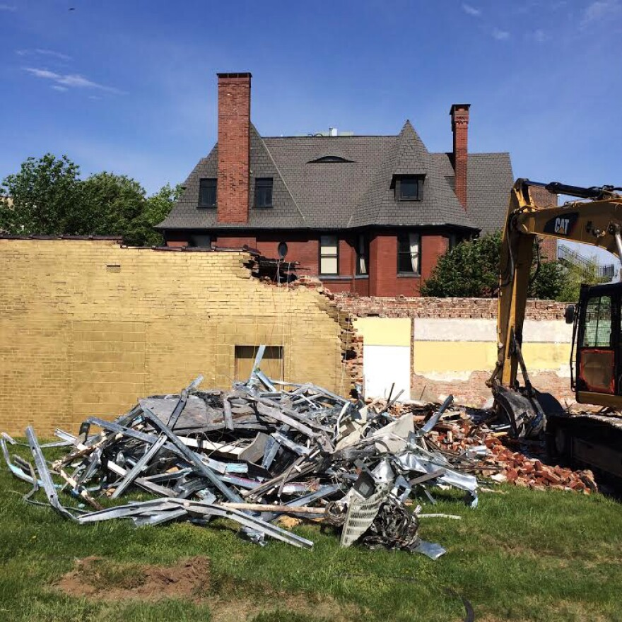 A pile of scrap metal sits in the foreground on a grassy lawn, behind it stands a brick wall painted gold and construction machinery.