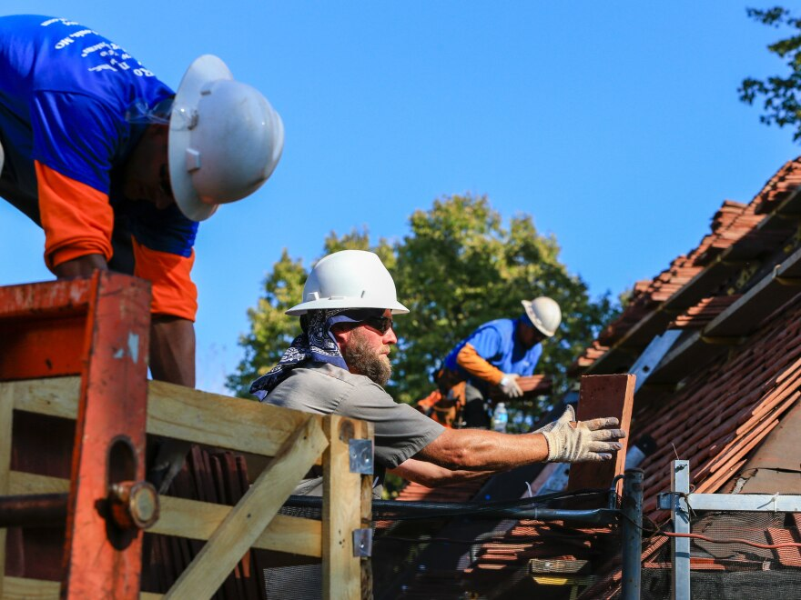 Construction workers lay tiles on the roof of a house in Boys Town, Neb.