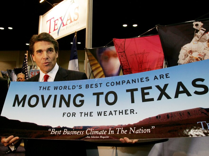 """Texas Gov. Rick Perry holds a sign promoting business in Texas, in San Antonio, on Nov. 8, 2004. Nearly a decade later, Perry is still touting the state's pro-business bent, including a <a href=""""http://www.nytimes.com/2013/10/02/us/texas-governors-trips-to-lure-jobs-stir-skepticism-over-motive.html"""">tour this summer</a> to several states."""