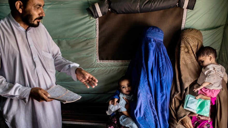Usman (right), 7 months, and Abdullah (left), 18 months, are held by their mothers while they wait to receive the polio vaccine at the Jalozai refugee camp near Peshawar, Pakistan.