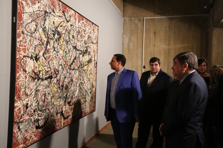 "Iranian Culture Minister Ali Jannati (right) looks at Jackson Pollock's ""Mural on Indian Red Ground"" (1950) during the opening ceremony of an exhibition at Tehran's Museum of Contemporary Art on Nov. 20."