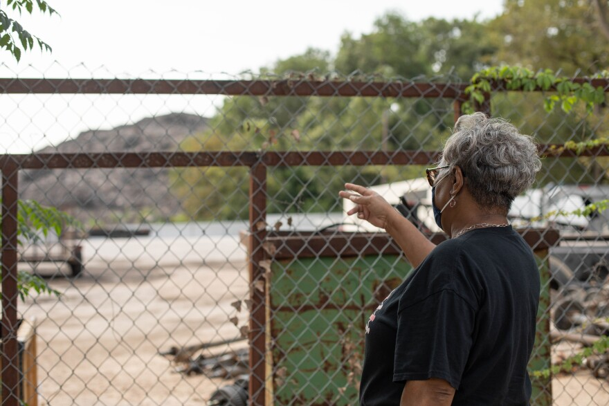 Marsha Jackson points at Shingle Mountain, a pile of trash and shingles she has been fighting to get rid off for years.