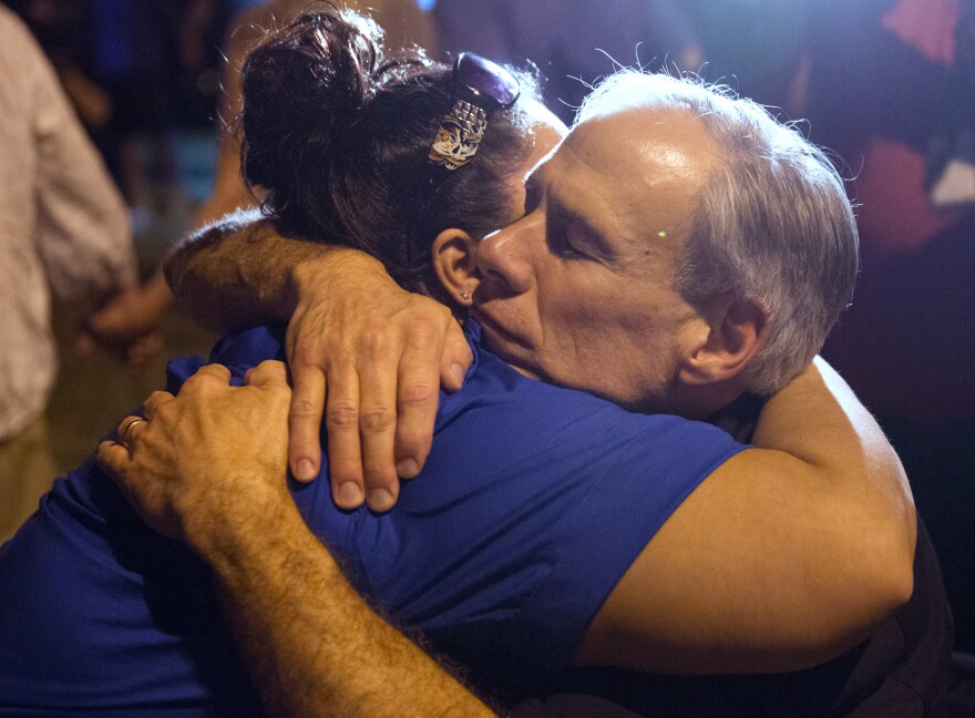 Texas Gov. Greg Abbott comforted a local resident during the candlelight vigil.