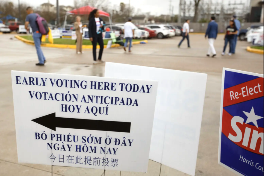 A sign pointing to an early voting center in Houston. The sign is displayed in several languages, including English, Spanish, Vietnamese and Chinese.
