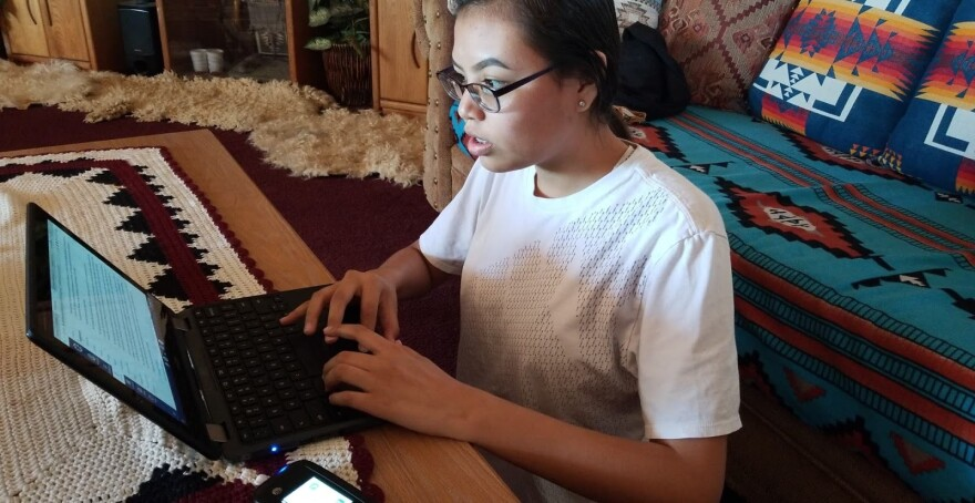 A young Navajo girl works on a laptop in a living room decorated with Native American weavings