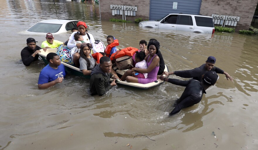 Residents evacuate their apartment complex Monday in Houston.