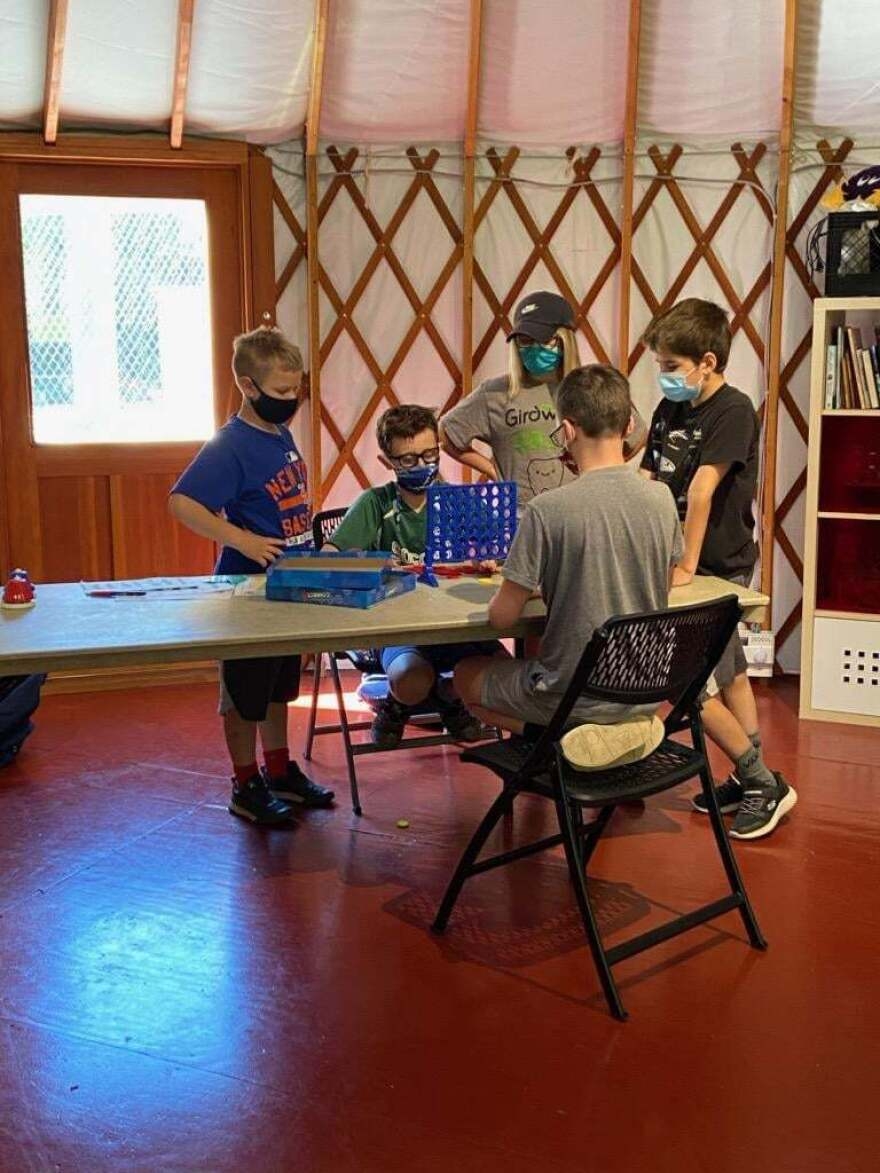 Photo of kids in masks playing a board game.
