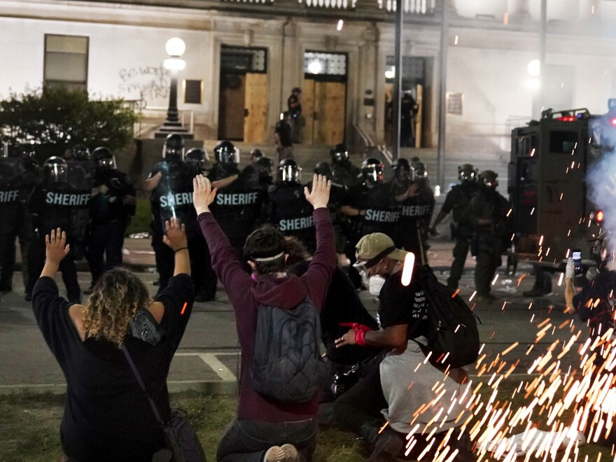 Police attempt to push back protesters outside the Kenosha County Courthouse late Monday. Protesters converged during a second night of clashes after the police shooting of Jacob Blake.