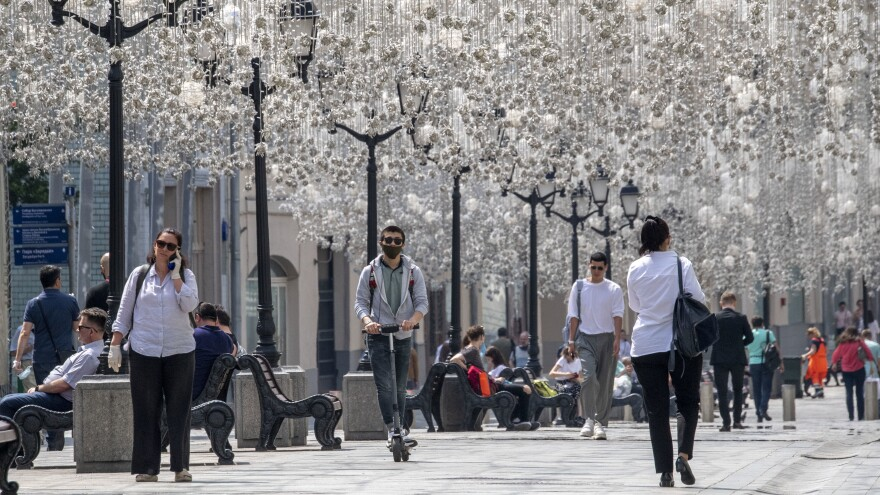People enjoy warm weather Monday in downtown Moscow. The mayor has announced the gradual lifting of the coronavirus lockdown in the Russian capital.