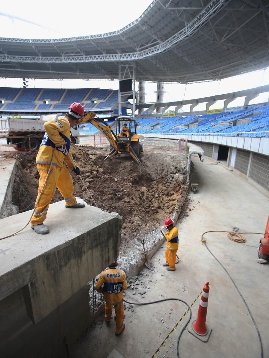 Construction workers building the Olympic Stadium in October 2015. While most venues are ready, or close to ready, costs have been higher than planned and the country is suffering from a recession. Organizers say they are looking for ways to cut costs.