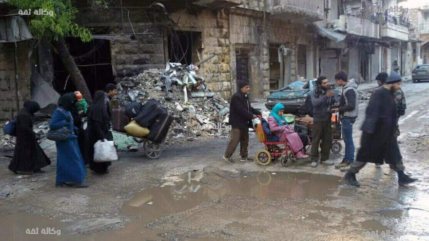 Civilians gather for evacuation from eastern Aleppo, Syria, on Thursday, in a photo released by a pro-opposition media group. Syrian activists said residents in eastern Aleppo are starting to board buses and ambulances, the first step in an evacuation that is part of the rebel enclave's effective surrender.