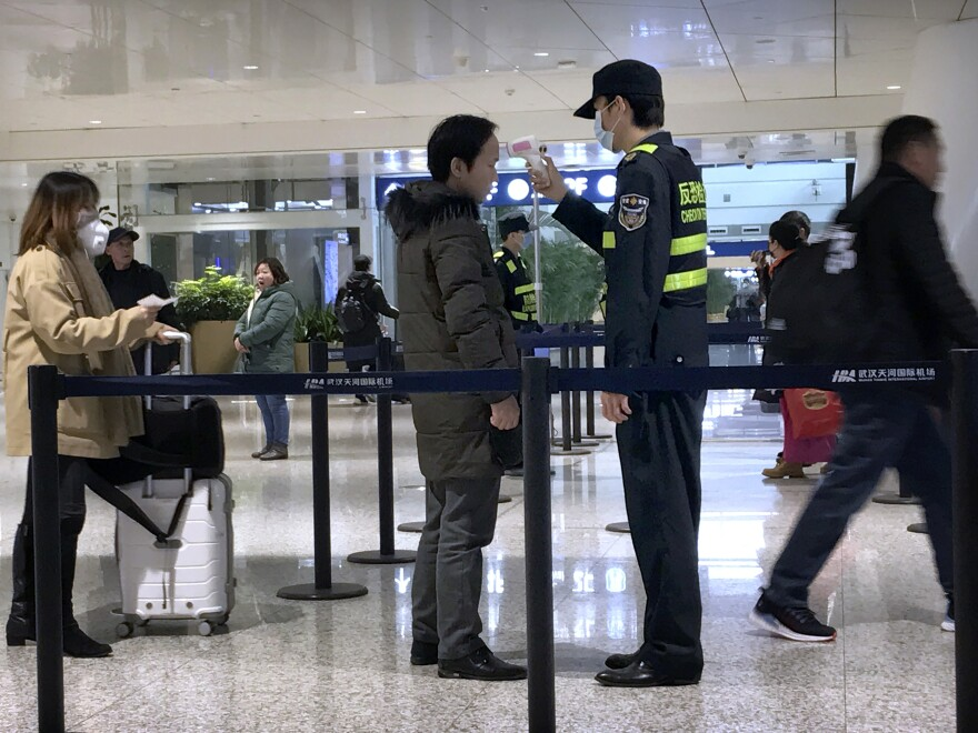 Airport officials screen for possible cases of the novel coronavirus at Wuhan Tianhe International Airport in Wuhan, China, where the illness originated.