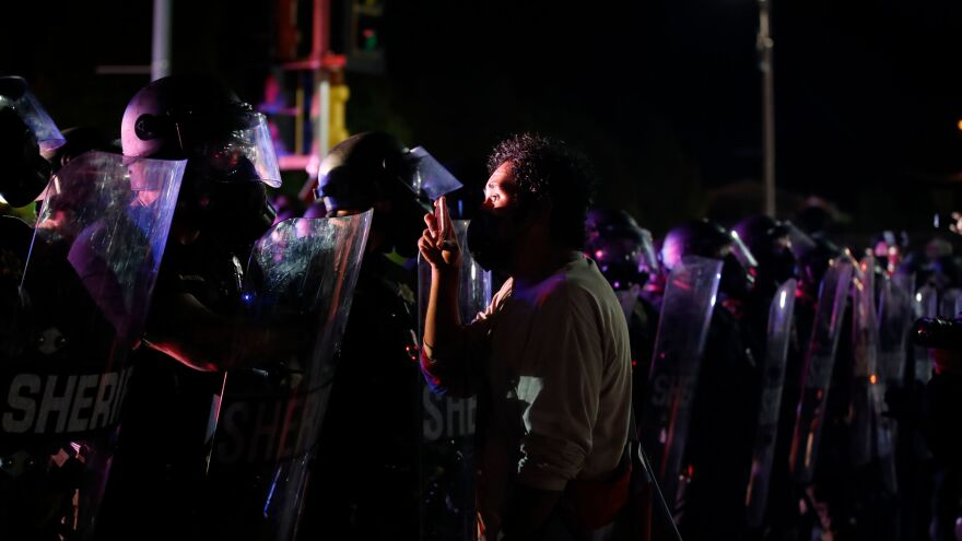 A protester stands face to face with police during demonstrations over the shooting of Jacob Blake in Kenosha, Wis., in August.