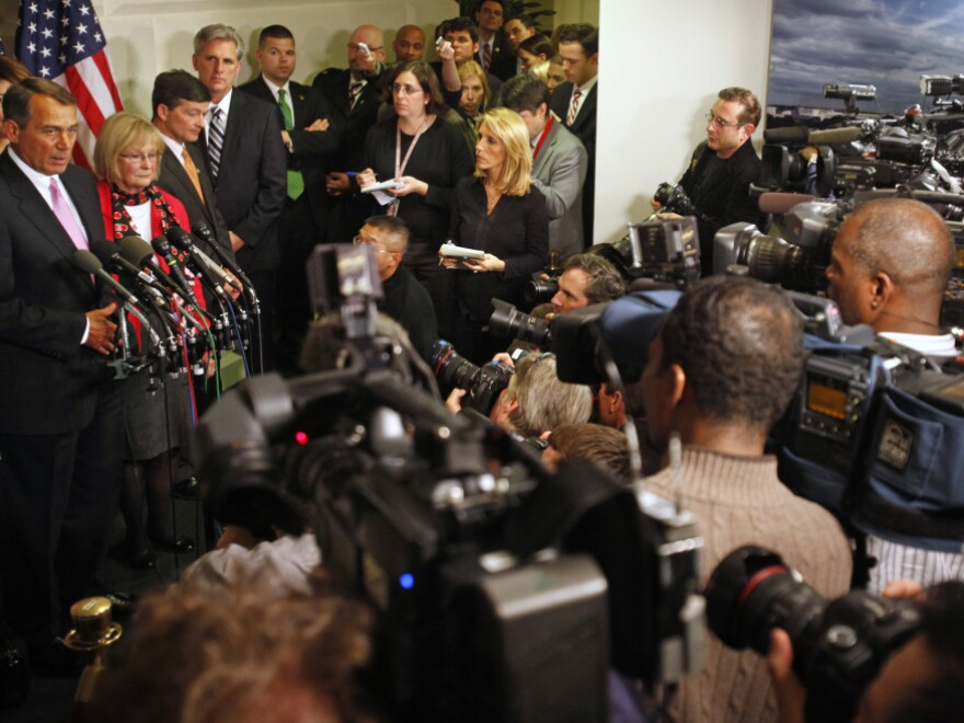 Surrounded by news media, House Speaker John Boehner announces a deal was reached, avoiding a government shutdown.