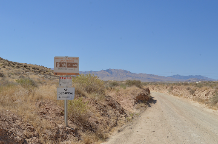 A photo of a dirt road with signs in the desert.