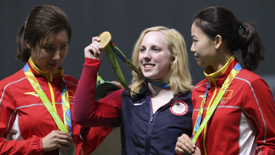 Ginny Thrasher (center) of the U.S. holds her gold medal for the women's 10-meter air rifle competition, the first gold awarded at the Rio Games. China's Du Li (left) won the silver and Yi Siling, also of China, won the bronze on Saturday.
