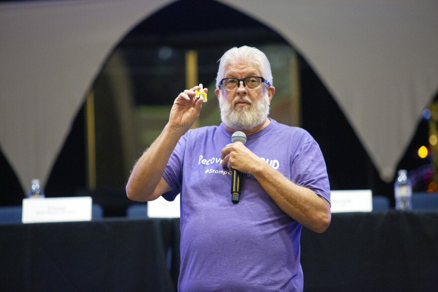 A man with a beard and wearing a purple shirt holds up a white, plastic applicator that goes into a nostril and sprays a drug that revives people who have overdosed on opioids.