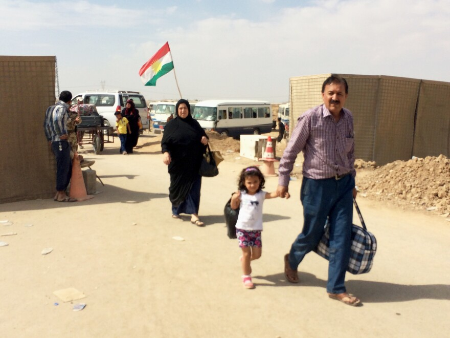 A family passes through Maktab Khaled in northern Iraq, the last Kurdish checkpoint before they make their way to Kirkuk. ISIS-controlled territory lies less than a mile away.