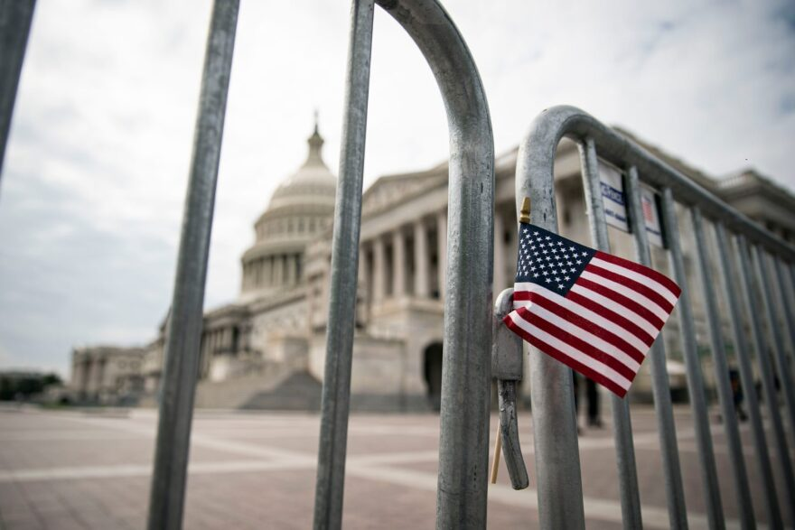 An American flag is placed on a fence outside of the U.S. Capitol building in Washington, DC.