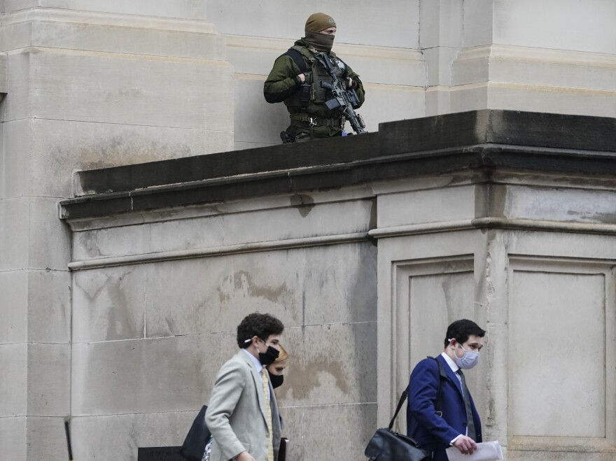 A member of the Georgia State Patrol SWAT team looks on as people walk by outside of the Georgia State Capitol after the opening day of the legislative session on Monday in Atlanta. State capitols across the country are under heightened security after the siege of the U.S. Capitol last week.