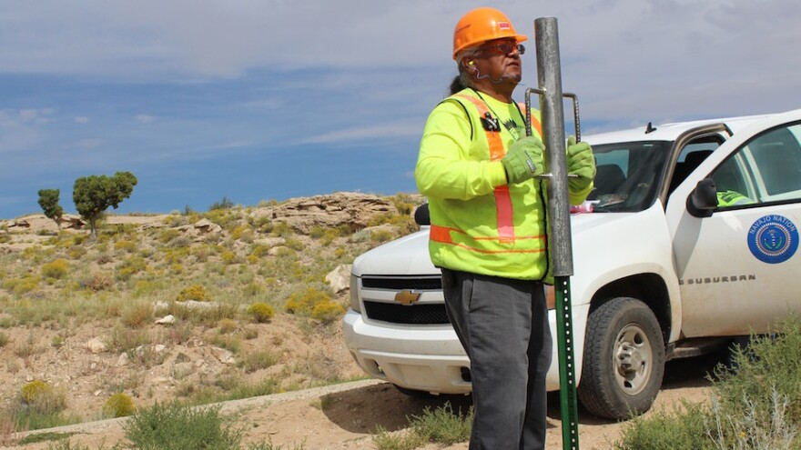 M.C. Baldwin, working for the Navajo Nation Rural Addressing Authority, installs a pair of street signs along BIA road 5020.