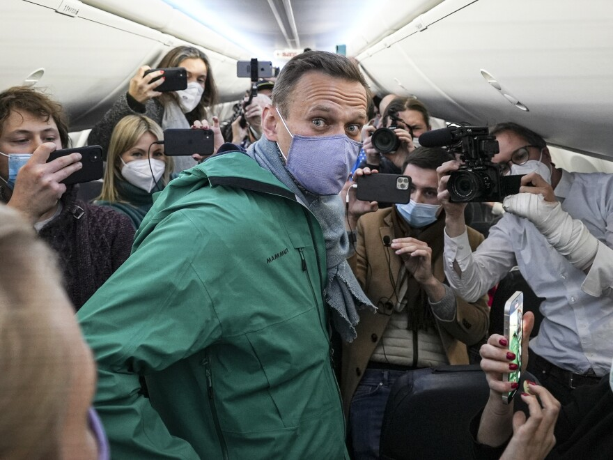 Alexei Navalny is surrounded by journalists on a plane Jan. 17 before a flight to Moscow at Berlin Brandenburg Airport. Navalny was arrested upon his return to Russia.