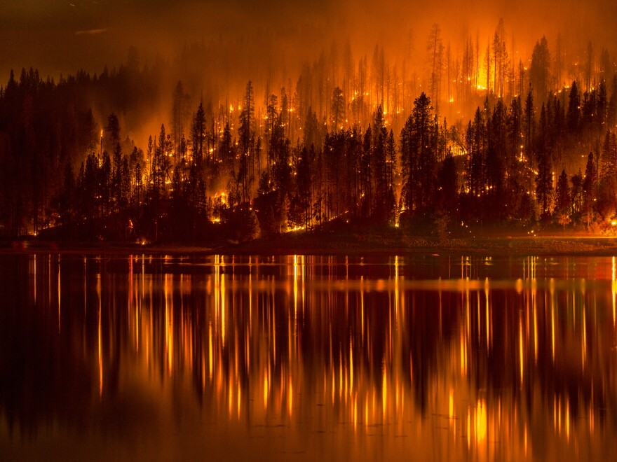 A photo from Sunday shows a wildfire as it approaches the shore of Bass Lake, Calif. Several blazes are being fueled by record drought conditions.