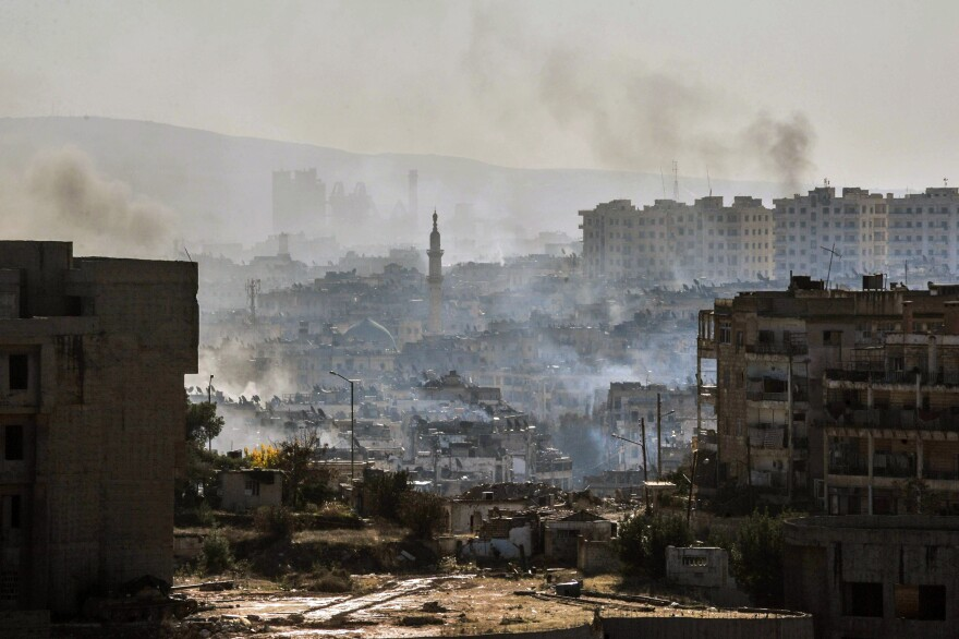 In this photo released by the Syrian official news agency SANA, smoke rises in an east Aleppo neighborhood in Syria on Thursday.