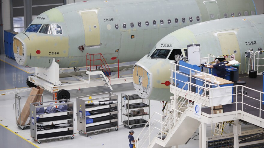 Employees work on Airbus SE A321 fuselages at the company's final assembly line facility in Mobile, Ala. in 2017.
