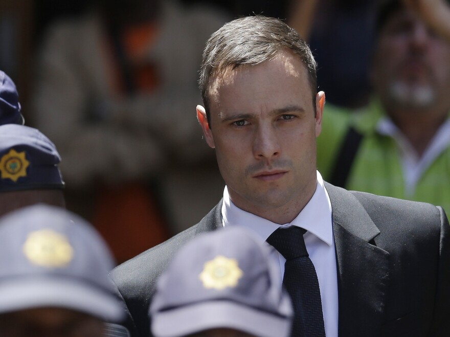 Oscar Pistorius is escorted by police officers as he leaves the high court in Pretoria, South Africa, in October 2014.